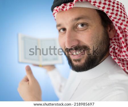 Arabic man holding Koran - stock photo