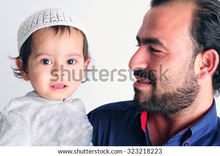 Arabic Muslim father looking proudly at his little boy - stock photo