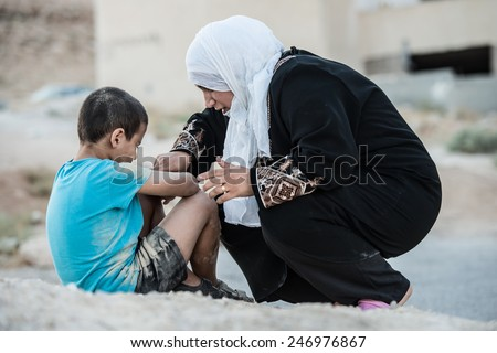 Arabic Muslim Middle Eastern poor woman with her son on dirty ground - stock photo