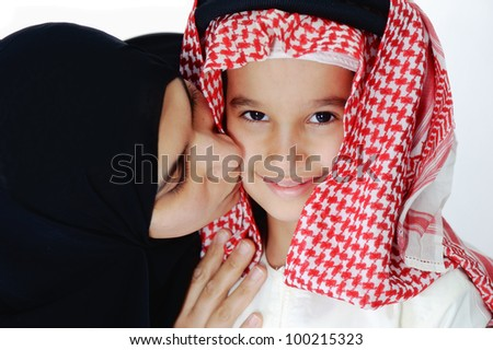 Arabic Muslim mother kissing her little son - stock photo