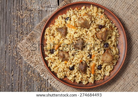 Arabic traditional national delicious rice food called pilaf cooked with fried meat, onion, carrot and garlic - stock photo