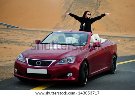 Arabic way dressed yang woman posing in red car in desert. - stock photo