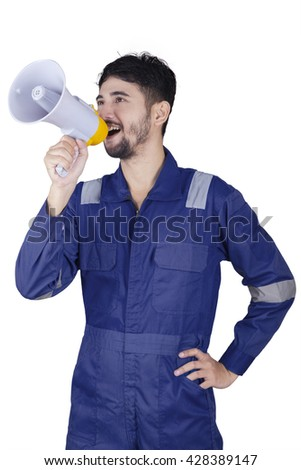 Arabic workshop worker wearing uniform and shouting with a megaphone in the studio - stock photo