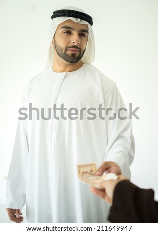 Arabic young businessman making deal and receaving money - stock photo