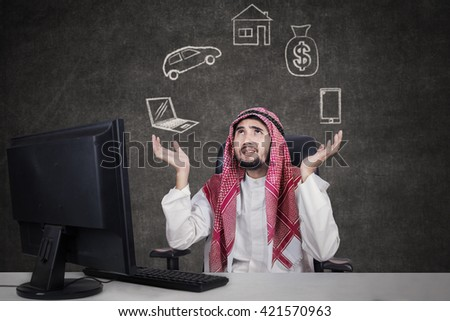 Arabic young businessman working with computer while wearing traditional clothes and thinking his dreams - stock photo
