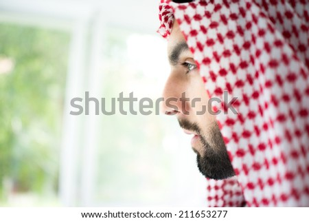 Arabic young sheikh looking trough the window - stock photo