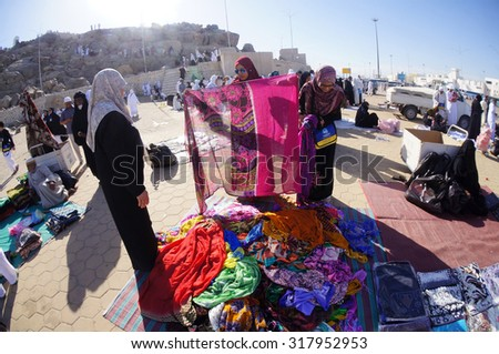 ARAFAT, SAUDI ARABIA-CIRCA MAY 2015:Two unidentified women bargaining clothes at Mount Arafat (or Jabal Rahmah) on May,2015 in Arafat,Saudi Arabia.Muslims believe it is here prophet Adam & Eve met - stock photo