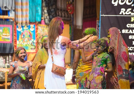 ARAMBOL, GOA, INDIA - MARCH 17: Unidentified people celebrates Holi festival in Arambol Main Street, GOA, India on March 17, 2014. It's a religious spring holiday and also known as Festival of Colours.  - stock photo