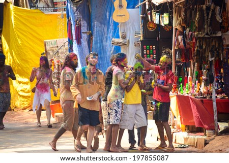 ARAMBOL, GOA, INDIA - MARCH 17: Unidentified people celebrates Holi festival in Arambol Main Street, GOA, India March 17, 2014. It's a religious spring holiday and also known as Festival of Colours.  - stock photo