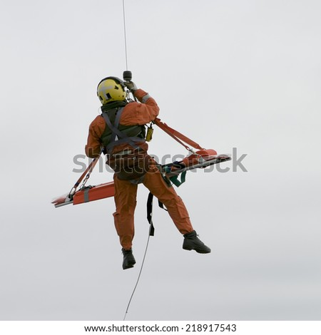 ARAN ISLANDS, IRELAND - JULY 2, 2006: An Irish coast guard search and rescue mission shows a dangling guardsman in an orange uniform bringing the stretcher up to the helicopter near the Aran Islands. - stock photo