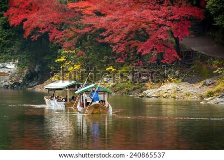 Arashiyama, Japan-25 Nov 2014: Group of Tourists cruising with blue jacket Japanese Ferryman in the River at Arashiyama on 25 Nov. - stock photo