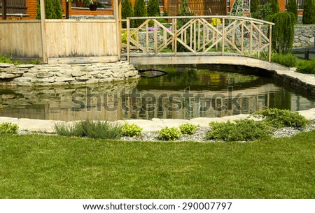 Arbor in garden with flowerbed, colorful plants and pond - stock photo