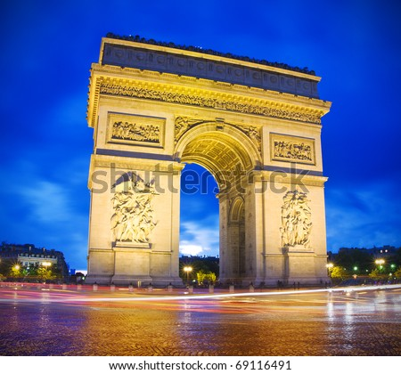 Arc de Triomphe (arch of triumph) in Paris by night - stock photo