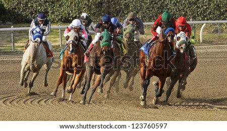 "ARCADIA, CA - JAN 5: A field of thoroughbreds gallops around the far turn in a claiming race at Santa Anita Park on Jan 5, 2013 in Arcadia, CA. Eventual winner is Aaron Gryder (red cap) and ""Tummel"". - stock photo"