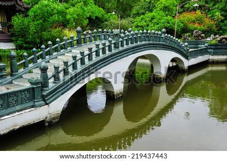 Arch bridge in the park. - stock photo