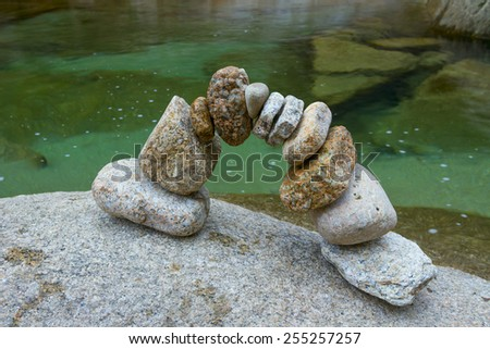 arch of granite stones on a background of water - stock photo