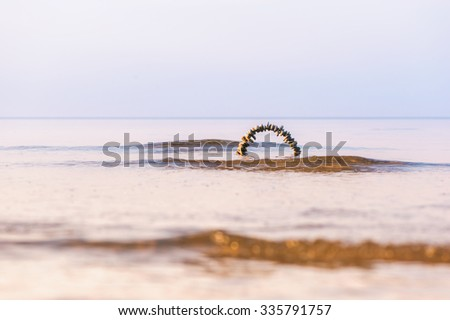Arch of pebbles on the surface of the sea - stock photo