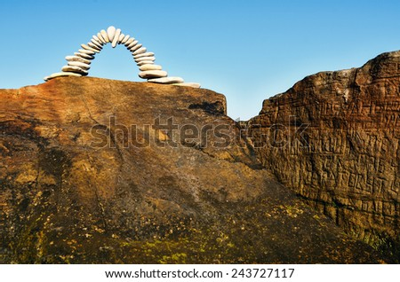 Arch of pebbles on the top of the rock - stock photo
