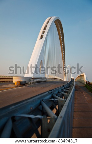 arch of suspended bridge over the highway - stock photo