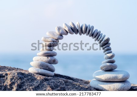 Arch of white pebbles in the balance on the seacoast - stock photo