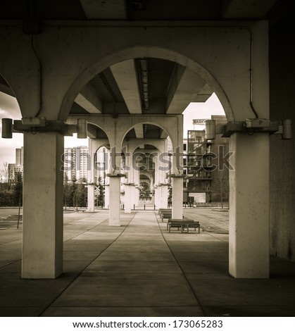 Arch supports under the walking bridge in Nashville, TN leading into the distance - stock photo