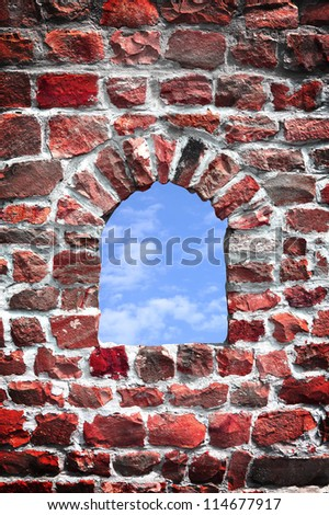 Arch window of old red stone fortress and blue sky - stock photo