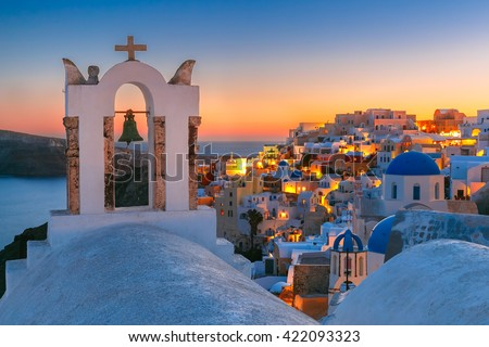 Arch with a bell, white houses and church with blue domes in Oia or Ia at sunset, island Santorini, Greece  - stock photo
