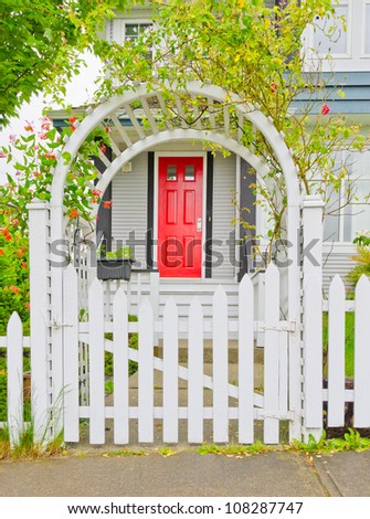 Arch wooden entrance with the fence, cowered with flowers - stock photo