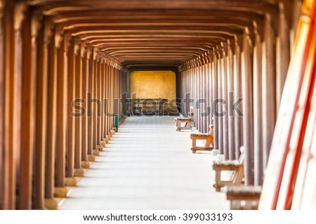Arched doorway of Hue citadel, Vietnam, Asia. Yellow stone wall with entrance to hall. Wooden benches along wall, red ceiling and columns. Famous destination for tourists. UNESCO Heritage site. - stock photo