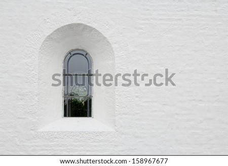 Arched latticed window in a white church wall - stock photo