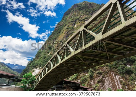 arched pedestrian bridge on a background of mountains - stock photo