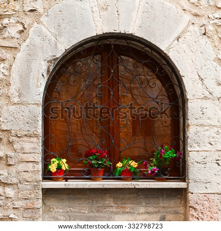 Arched Window Decorated With Fresh Flowers in Italy - stock photo