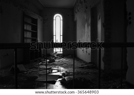 Arched window empty bookcase and dirty floor in abandoned house interior. Black and white. - stock photo