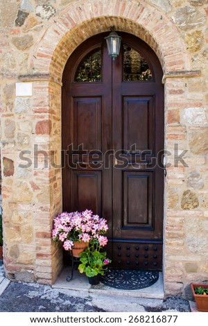 Arched wooden door in a stone facade - stock photo