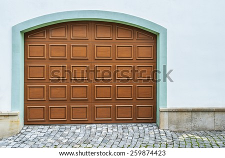 Arched wooden garage doors in a modern house. - stock photo