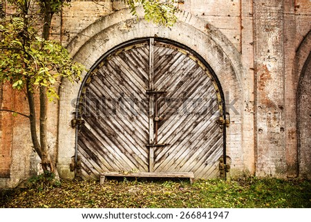 Arched wooden garage doors in a old house. - stock photo