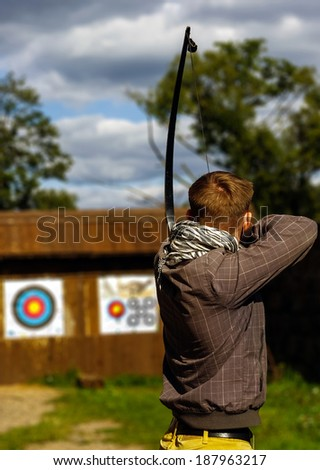 Archer aiming at the target, focused and concentrated  Objectives / Goals / Success / Aim / Target / Archery / Business / Challenge Background - stock photo