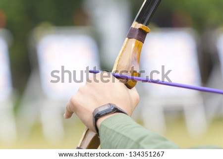 archer holds his bow aiming to the target. - stock photo