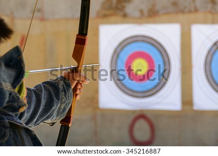 archer is aiming the arrow of the bow at the target - stock photo
