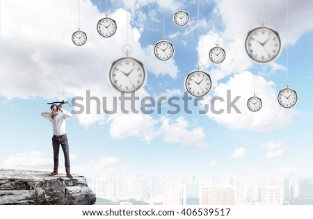 Archer standing on the edge of a cliff, aiming at suspended clocks on sky background - stock photo