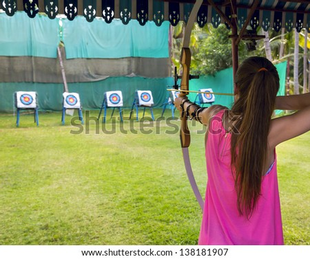 Archer young woman pulls the bowstring and arrow, aiming at a target - stock photo