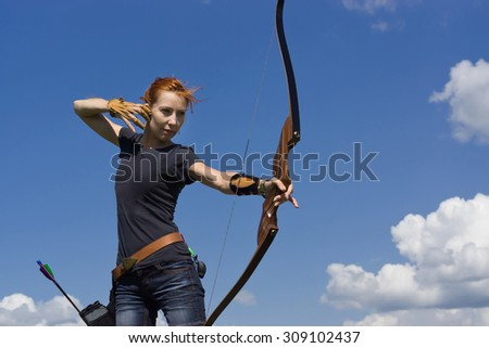 Archery woman bends bow archer target narrow in the summer field - stock photo