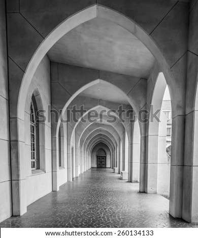 Arches leading toward a door over a tile walkway - stock photo