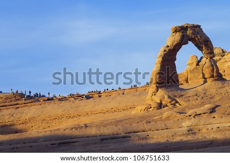 ARCHES NATIONAL PARK, USA - NOVEMBER 9: A group of tourists during sunset at Delicate Arch sunset on November 9, 2008 in Arches National Park, USA. It is the most famous arch in the park. - stock photo