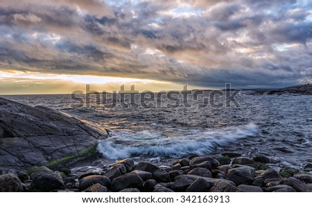 Archipelago sunset with cloudy sky with sun shining trough the clouds and light up the horizon - stock photo