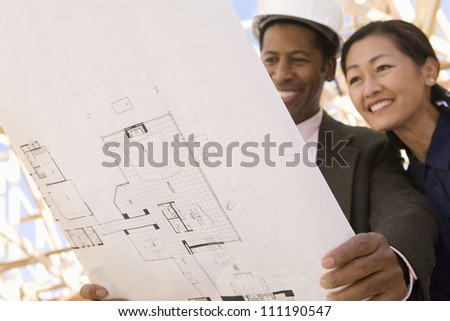 Architect and a happy woman examining a blueprint at a construction site - stock photo