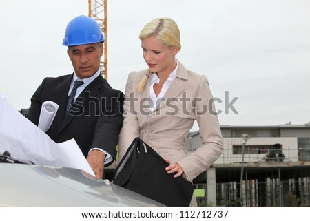 Architect and assistant visiting construction site - stock photo