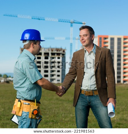 architect and construction engineer standing and shaking hands on construction site outdoors - stock photo
