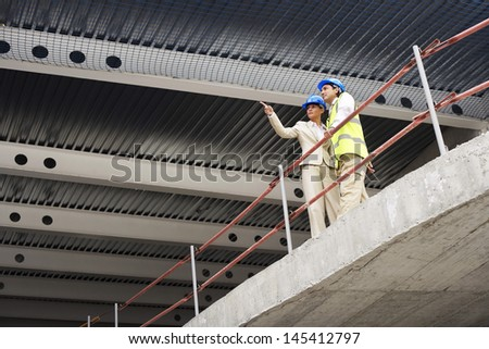 Architect and construction manager discussing plans at site - stock photo