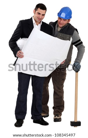 Architect and construction worker looking at plans - stock photo